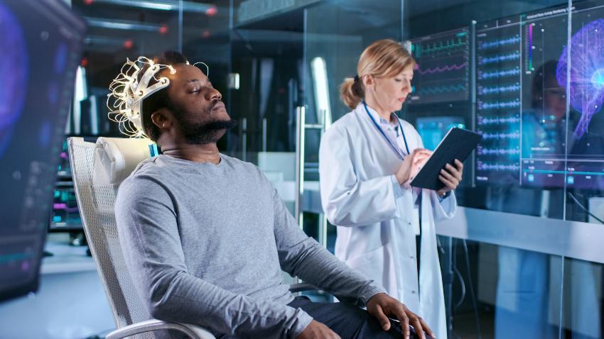 Mann sitzt mit geschlossenen Augen in einem Stuhl, Hirnströme werden im Schlaf gemessen - Was passiert im Schlaf mit Körper und Gehirn?