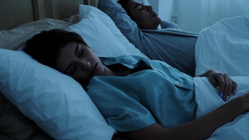 Junges Ehepaar schläft im Bett - Was passiert im Schlaf mit Körper und Gehirn?