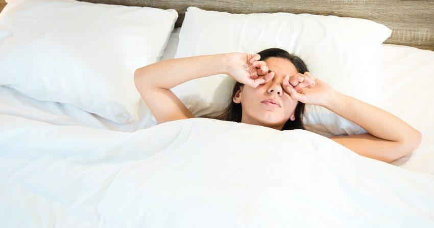 Frau reib sich den Schlafsand aus den Augen