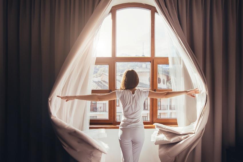 Frau schiebt Vorhang auf - Schlafzimmergestaltung