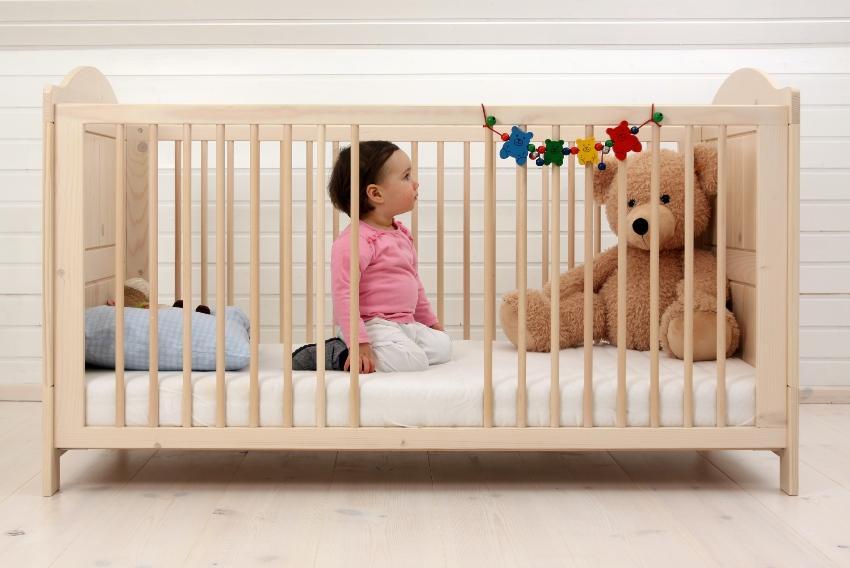 Baby im Bett mit Stofftier - Gitterbett für Babys