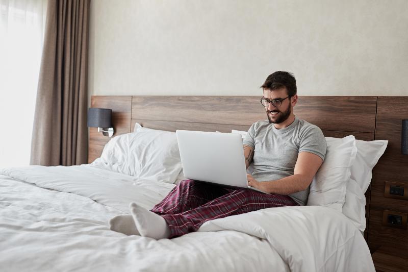 Ein Mann arbeitet in seinem Bett, während er auf seinem Laptop schreibt, lehnt er bequem am Kopfteil des Bettes