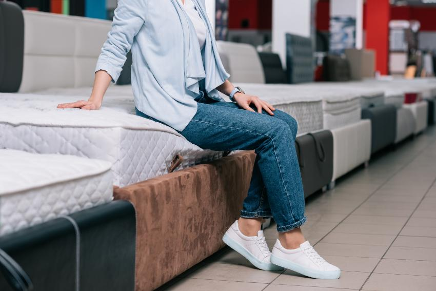 Eine junge Frau sitzt in einem Bettgeschäft auf einer Matratze, die deutlich einsinkt Einlegetiefe
