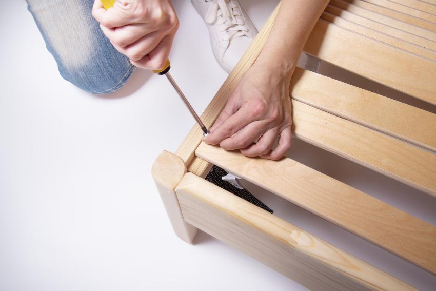 Ein Mann schraubt den Lattenrost an einem Holzbett fest Einlegetiefe