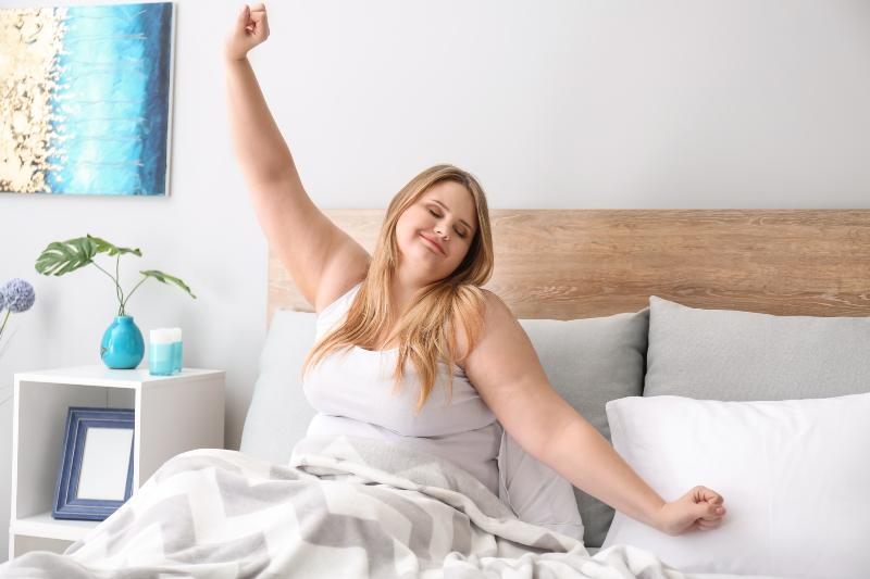 Eine korpulente Dame streckt sich nach dem Aufwachen in ihrem Bett Matratzen in Sondergrößen
