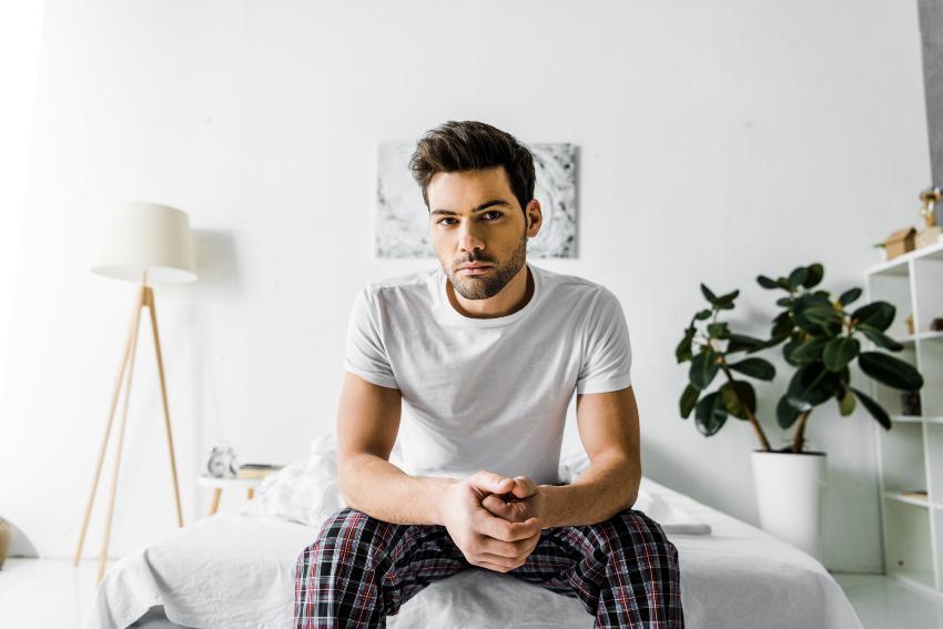 Ein junger Mann sitzt auf dem Bettrand, seine Unter- und Oberschenkel bilden einen 90°-Winkel optimale Betthöhe