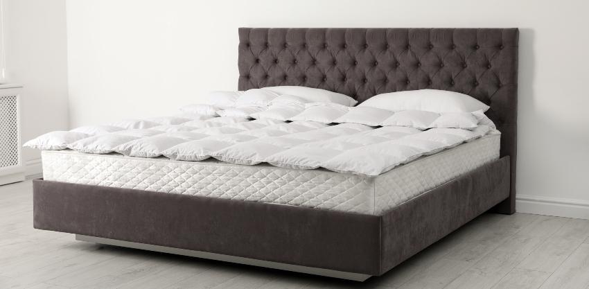 Ein gemütliches Bett mit einer hohen Matratze und einem Topper obenauf