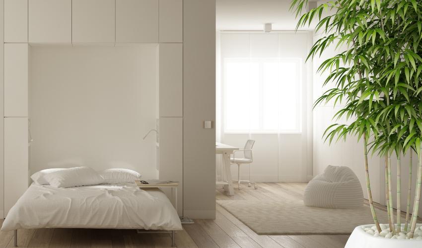 Ein Bett, das sich bei Bedarf in eine Wand einklappen lässt, in einem kleinen Wohn- und Schlafzimmer Schlaf- und Wohnzimmer in einem kleinen Raum