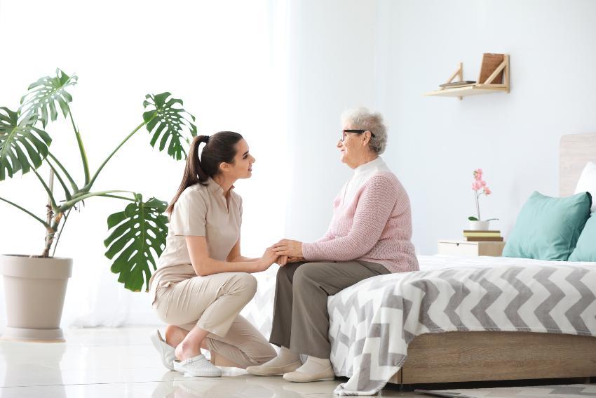 Eine junge Frau kniet vor dem Bett einer Seniorin und hält liebevoll ihre Hand optimale Betthöhe