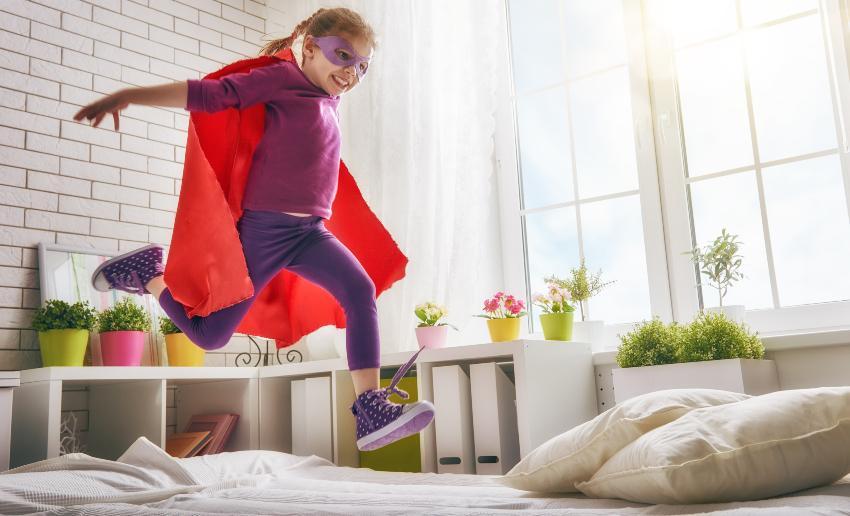 Ein Kind im Superhelden-Kostüm tobt mit Straßenschuhen im Bett