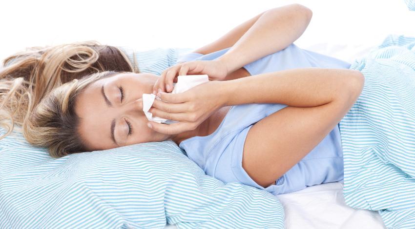 Eine Frau liegt im Bett und putzt ihre Nase, sie leidet offensichtlich an eine Milbenallergie