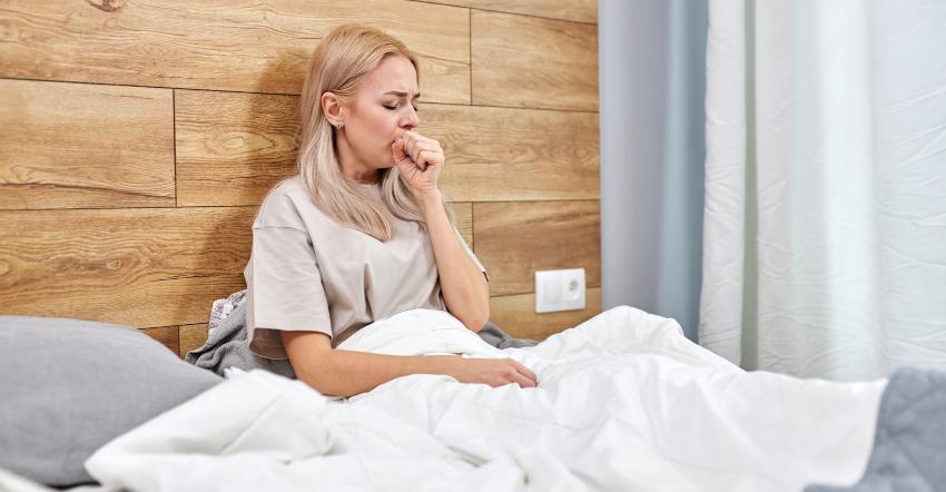 Eine Frau sitzt aufrecht im Bett und hustet, sie leidet offensichtlich unter einer Allergie Naturhaarbettdecken