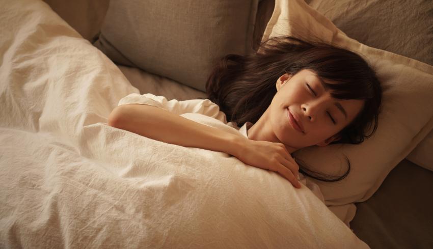 Eine Frau schläft gut zugedeckt im Bett und lächelt dabei Naturhaarbettdecken