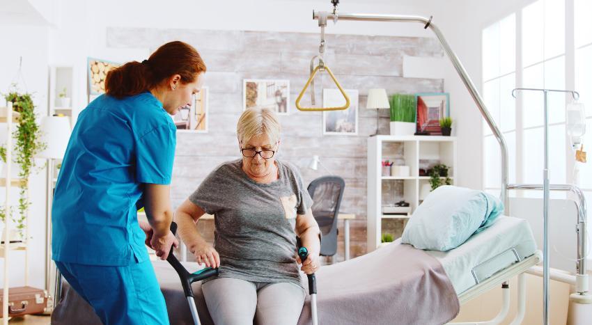 Eine Krankenschwester hilft einer älteren Dame auf, die auf dem Bett sitzt Matratzenkern