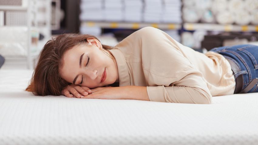 Eine Frau testet eine Matratze in einem Bettgeschäft Matratzenberater