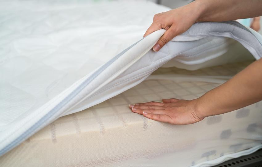 Jemand hat den Bezug der Matratze angehoben und testet mit der Hand die Festigkeit des Matratzenkerns