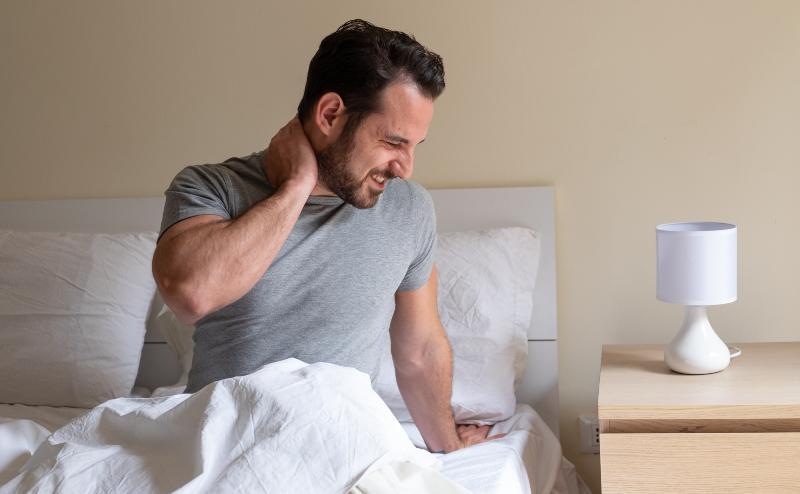 Ein Mann sitzt im Bett und hält sich den schmerzenden Nacken