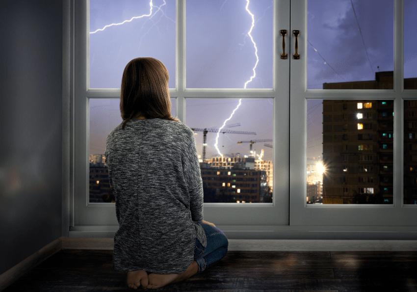 Eine junge Frau betrachtet durch ein Fenster ein Sommergewitter Sommerbettwäsche