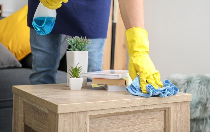 Mann reinigt kleinen Tisch