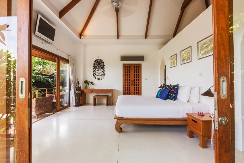 Doppelbett in einem Raum mit viel Licht und offener Tür - Leichte Sommerbettlaken sind bei Hitze angenehmer