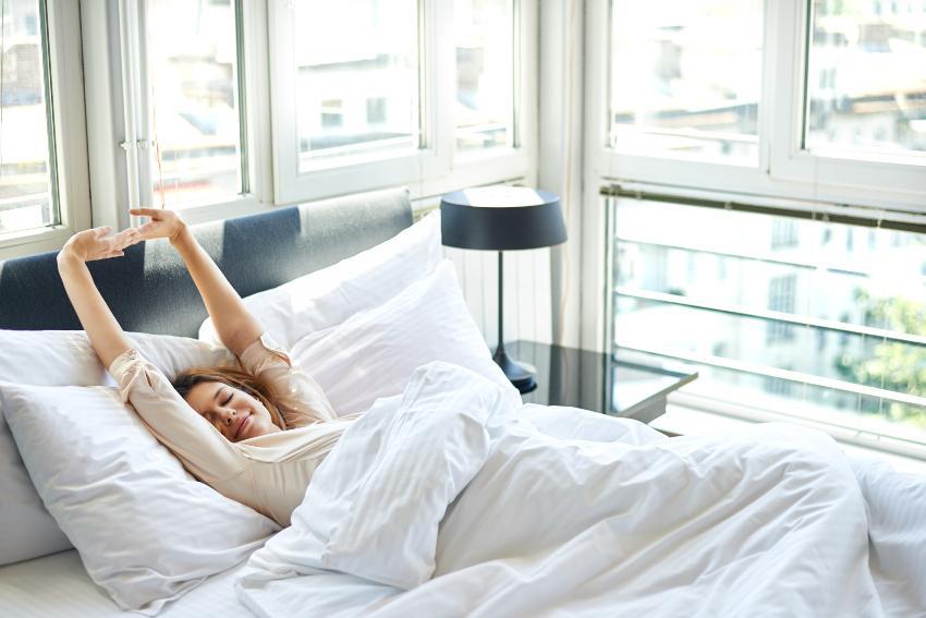 Eine junge Frau steckt sich genüsslich im Bett Lattenrost stabil