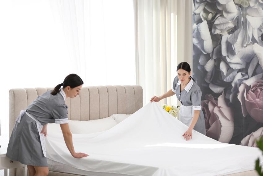 Angestellte beziehen ein Bett (im Hotel)