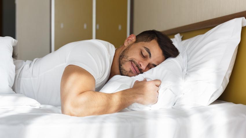 Ein muskulöser Mann schläft auf dem Bauch im Bett Punktelastizität vs. Flächenelastizität