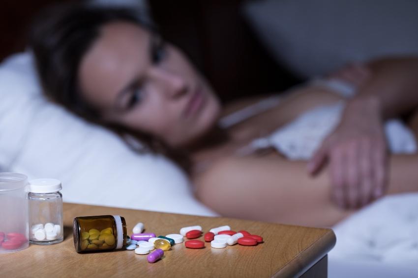 Frau liegt wach im bett, Tabletten am Nachttisch - Nachts aufwachen ist weitverbreitet