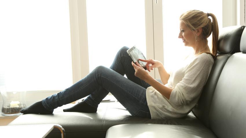 Eine Frau sitzt auf dem Sofa und benutzt ihr Tablett