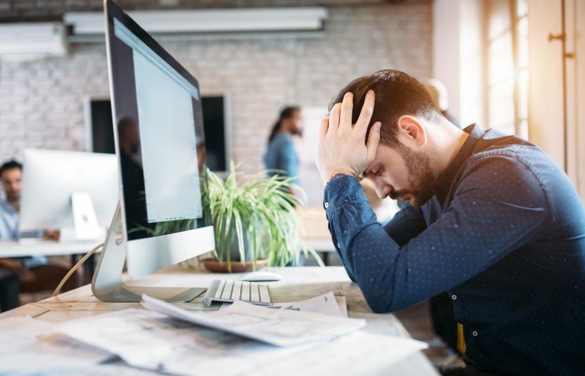 Mann sitzt gebeugt am Arbeitsplatz - Nachts aufwachen als Konsequenz aus stressiger Arbeit