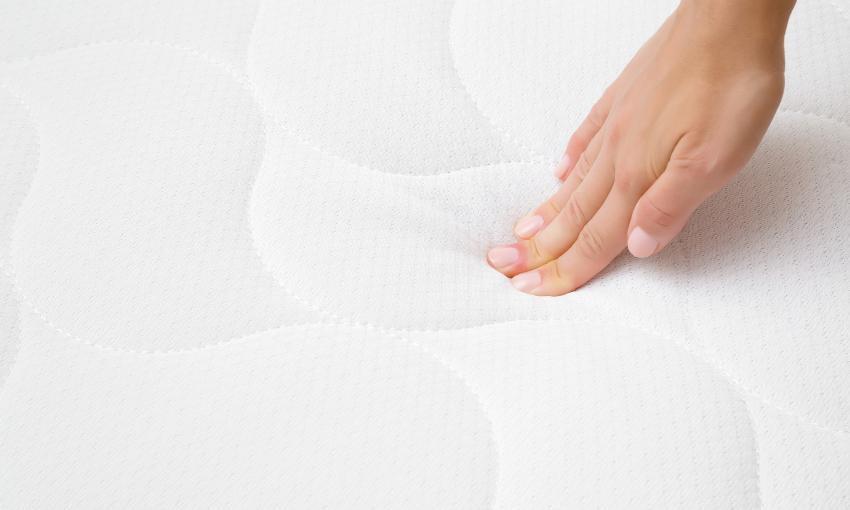 Jemand drückt mit den Fingerspitzen der Hand auf eine Matratze, so lässt sich leicht überprüfen, ob die Unterlage punktelastisch ist