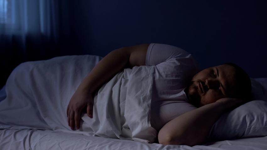 Ein korpulenter Mann liegt in Seitenschläferposition im Bett und schläft Punktelastizität vs. Flächenelastizität