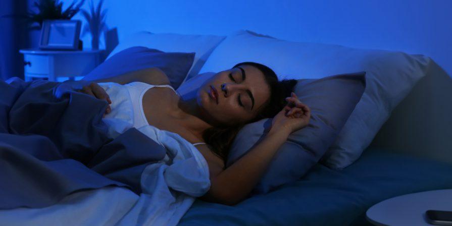 Frau schläft im Bett - Melatonin regelt den Schlaf