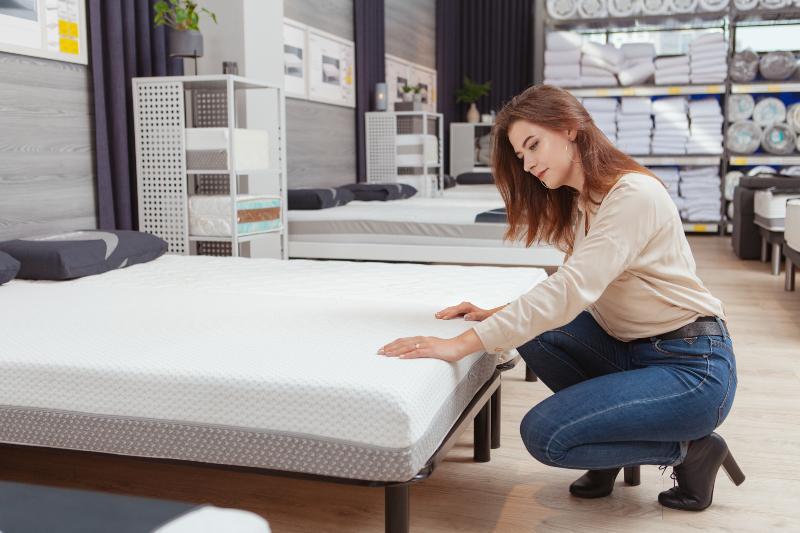 Frau prüft Matratze im Möbelhaus - Stauchhärte bei Matratzen