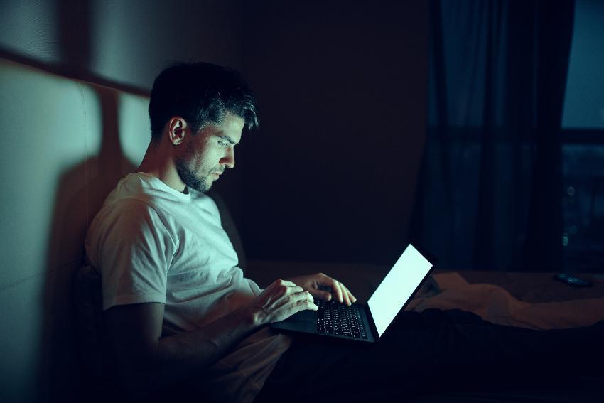 Mann sitzt im Bett mit hell leuchtendem Laptop