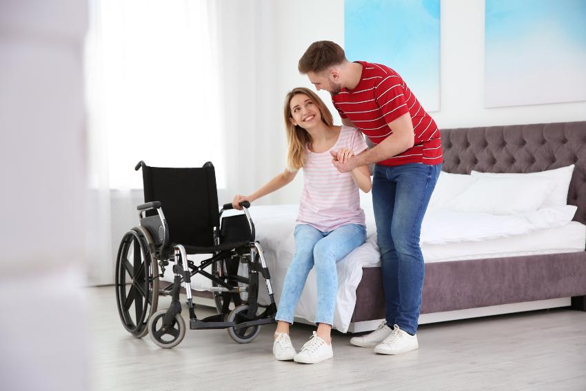 Frau sitzt im Bett - Mann hilft beim Aufstehen