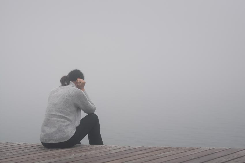 Frau mit Depressionen sitzt am nebeligen Seeufer