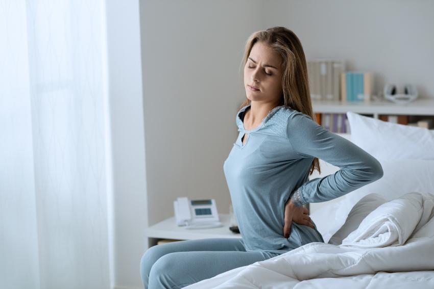 Frau hält sich morgens im Bett den Rücken vor Schmerzen - Hinweis auf eine alte Matratze