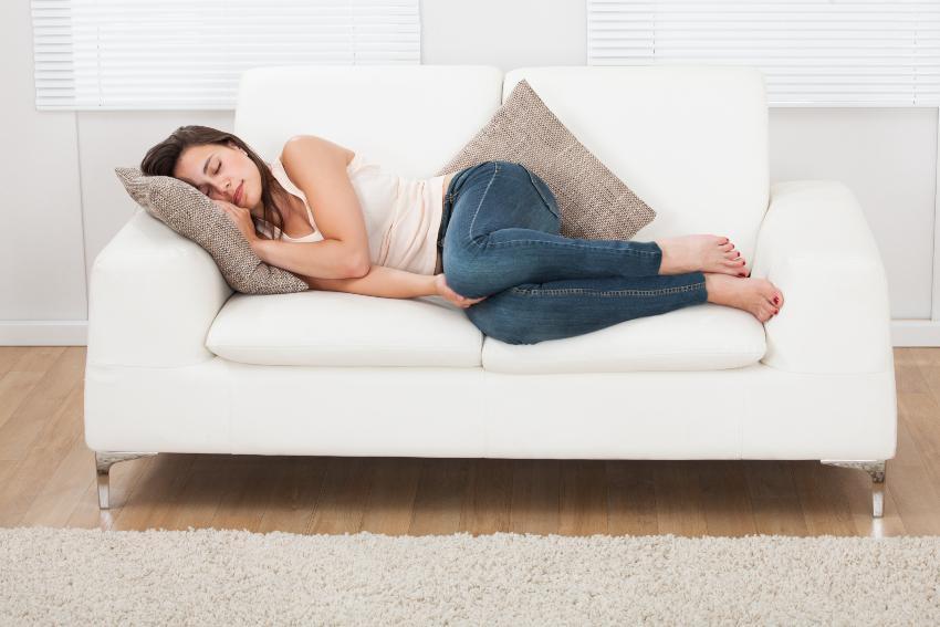 Frau schläft auf Couch - Schlaf und Depression können zusammenhängen
