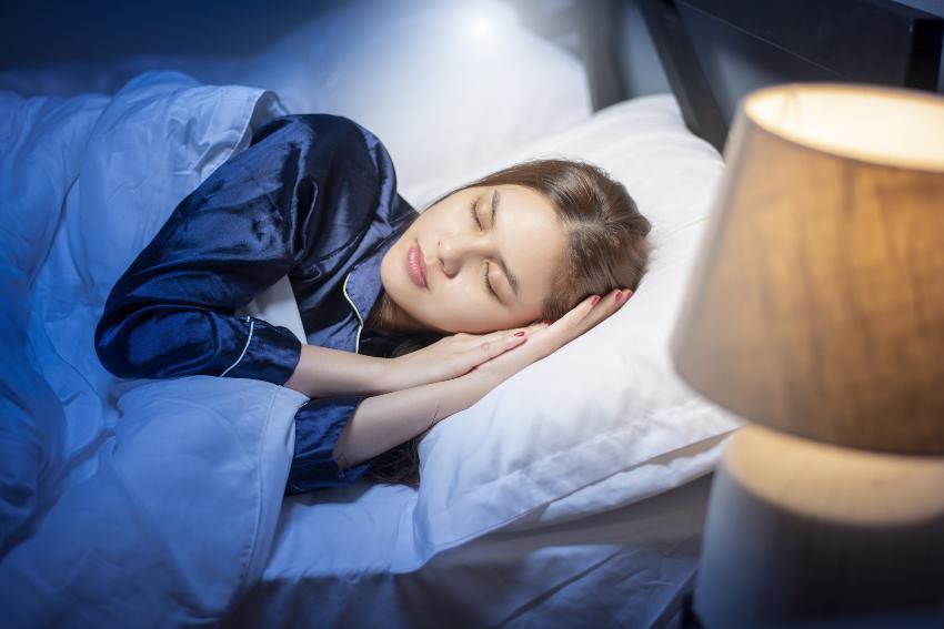 Frau schläft mit eingeschalteter Lampe