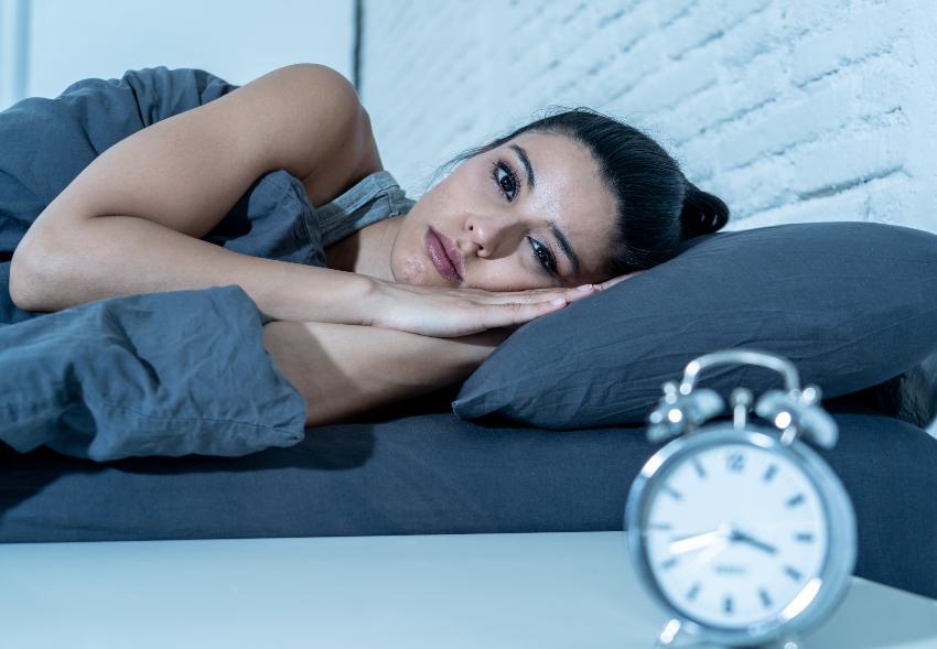 Frau liegt schlaflos im Bett - Zusammenhang von Schlaf und Depression