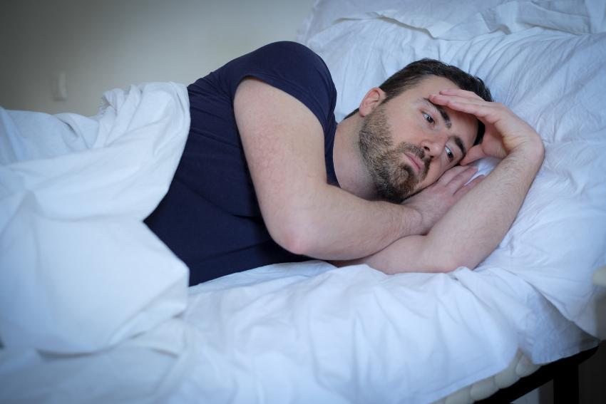 Mann liegt schlaflos im Bett