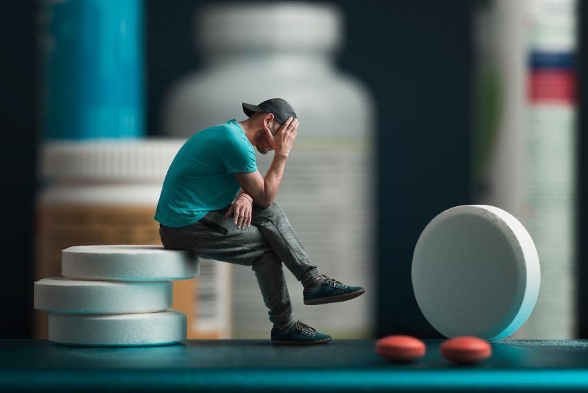 Mann sitzt symbolisch auf Tabletten - Depression und Medikation