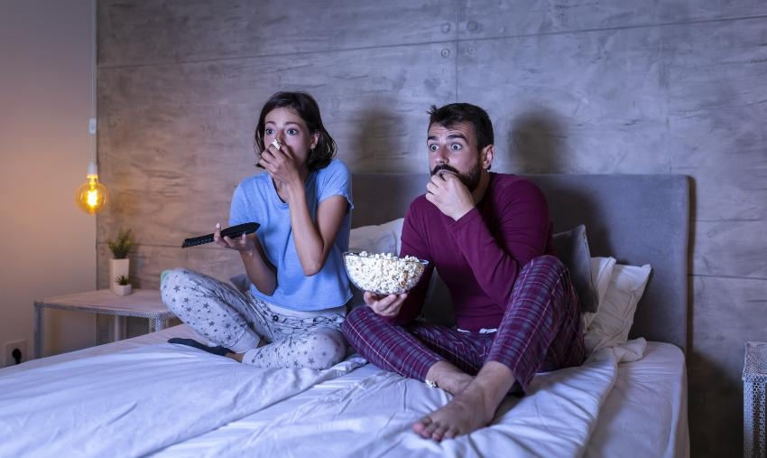 Junges Paar sieht fern im Bett - offenbar einen Horrorfilm oder Ähnliches