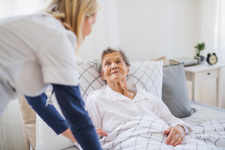 Alte Dame liegt im Bett, Pflegerin in der Nähe - ein elektrischer Pflegelattenrost kann hilfreich sein