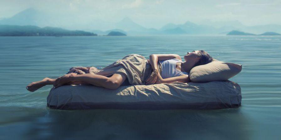 Frau schläft auf Bett in einem See - Waterlily® Matratzen