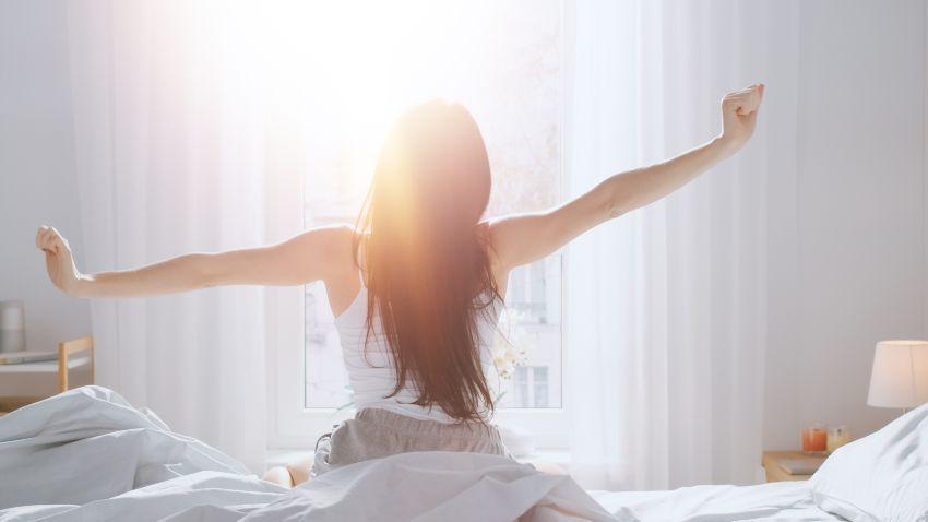 Junge Frau wacht ausgeschlafen auf