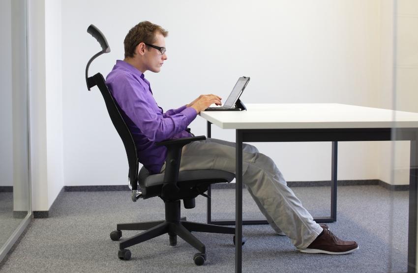 Mann sitzt in ungesunder Haltung am Schreibtisch - Nächtliche Wadenkrämpfe können Folge schlechter Haltung sein