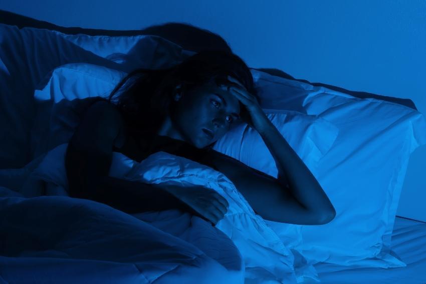 Junge Frau liegt im Bett und kann nicht schlafen - Schlaf fördern ist möglich