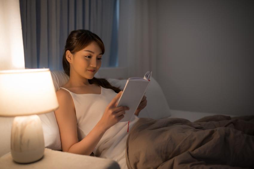 Frau liest Buch im Bett